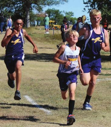 ABOVE LEFT: Dupree's Tripp Schrempp (L) and Case DePoy converge on either side of a Kadoka runner as they approach the finish line in cross country action at the LMC meet Saturday. Photo by Patty Peacock